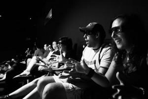 Pubblico al cinema guarda, munito di occhiali, con stupore un film in 3 dimensioni